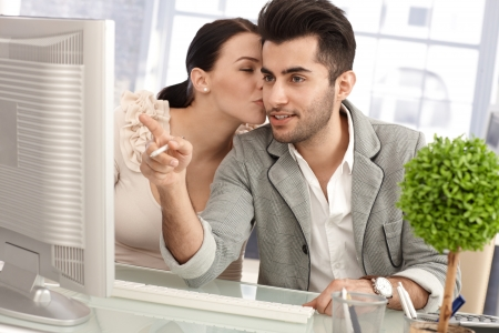 be kissed: Young colleagues flirting in workplace, woman kissing man while working together.