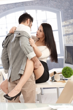 sex couple: Young couple having sex at workplace, on top of desk.
