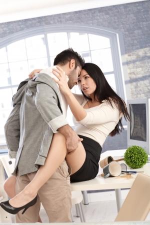 sexuales: Atractiva pareja joven teniendo sexo en la oficina, besando y abrazando.