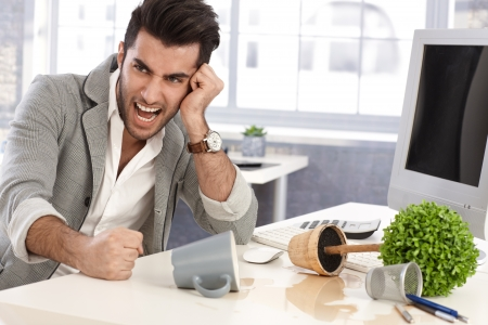 clenched: Young man shouting at workplace, hitting desk with anger by clenched fists. Stock Photo