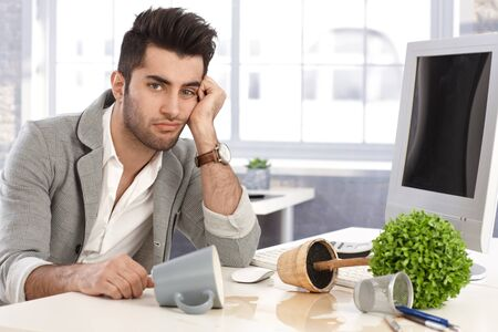 Young businessman sitting at desk desperate after burst of anger. Stock Photo - 17083800