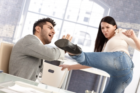 Young couple fighting, woman kicking man. Relationship crisis. Stress at workplace.