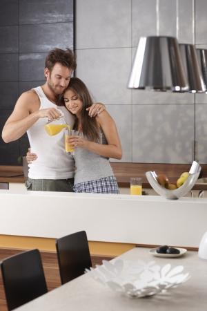 Young loving couple having orange juice in the morning at kitchen.
