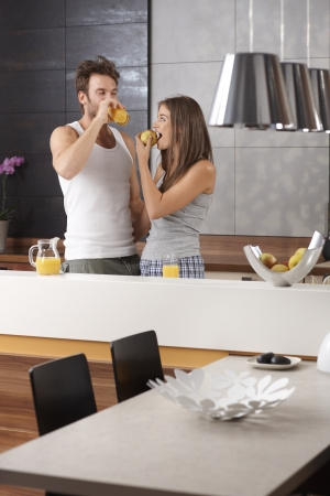 nighty: Morning picture of young couple in the kitchen with apple and orange juice. Stock Photo
