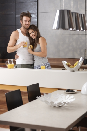 nighty: Portrait of happy loving couple in the morning at the kitchen. Stock Photo