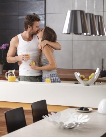 pijama: Joven pareja de enamorados bes�ndose en la cocina por la ma�ana, desayunando.