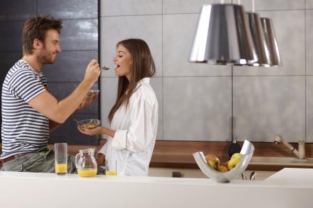 desayuno romantico: Joven pareja rom�ntica tener el desayuno en la cocina.