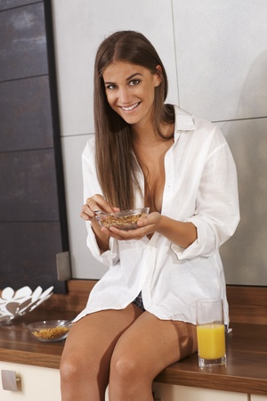 Beautiful happy girl having breakfast cereal on kitchen counter     photo