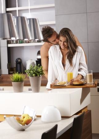 over packed: Joven pareja de enamorados que se besan en la ma�ana sobre la bandeja del desayuno completamente lleno. Foto de archivo
