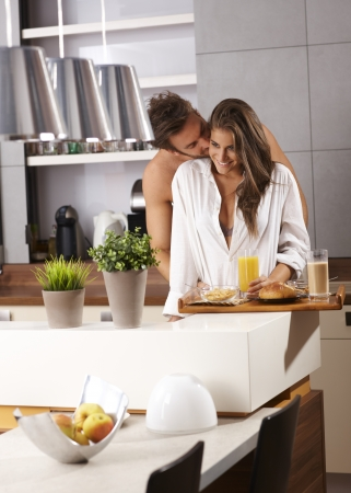 over packed: Young loving couple kissing in the morning over fully packed breakfast tray