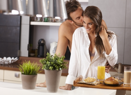 semi nude: Loving couple kissing in the kitchen in the morning   65533; Stock Photo
