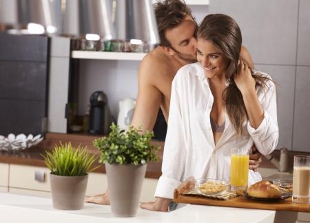 couple amoureux: Loving couple s'embrassant dans la cuisine le matin.