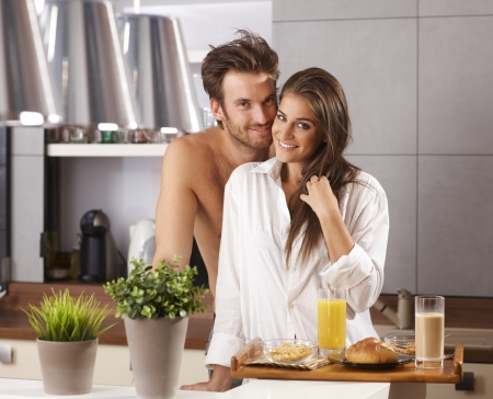 semi nude: Morning portrait of happy loving couple in the kitchen with breakfast   65533; Stock Photo