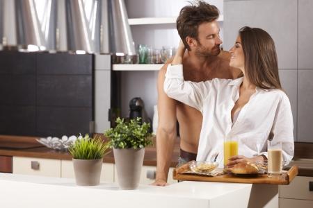 be kissed: Felice coppia di innamorati baciare in cucina la mattina.