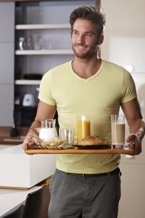 Handsome young man walking with breakfast tray in the morning   65533; Stock Photo - 17098449