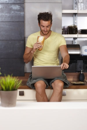 concentrating: Young man sitting on kitchen counter using laptop computer, having sandwich   65533;
