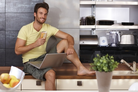Handsome young man sitting on kitchen counter, using laptop, having sandwich, smiling   65533; photo