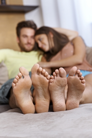 female feet: Young couple lying on sofa, relaxing  Focus on feet