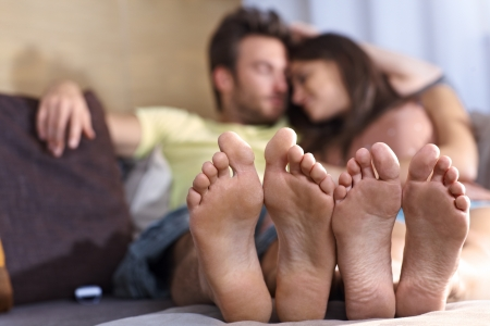 Young loving couple lying on sofa at home, relaxing in the afternoon  Focus on feet     photo
