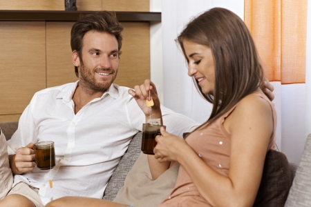 couple couch: Young loving couple having tea at home, smiling. Stock Photo