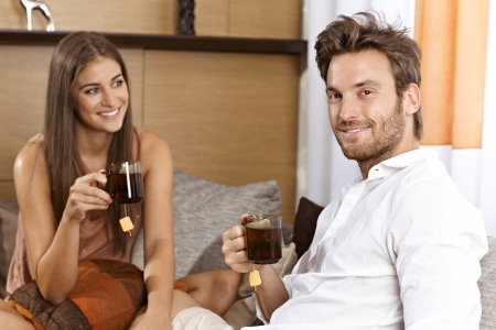 Attractive couple sitting on sofa at home, drinking tea, smiling happy   65533; photo