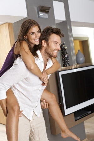 carry: Happy couple enjoying new home, piggyback ride   65533; Stock Photo