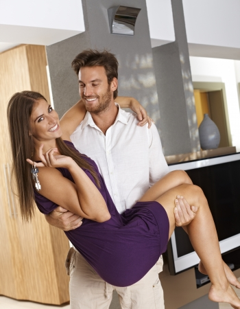 Attractive young couple enjoying new home, smiling happy  Man holding woman in his arms   65533; Stock Photo - 17098477