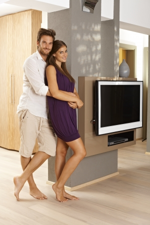 Attractive young couple standing in living room of stylish home, smiling happy