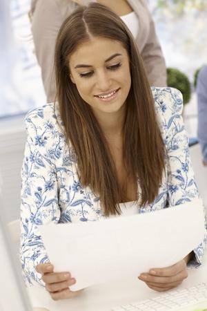 revisando documentos: Empresaria bastante joven sentado en el escritorio, leyendo periódicos, sonriendo.