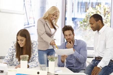 revisando documentos: Los jóvenes que trabajan en oficina brillante.