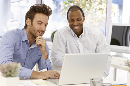 man using computer: Young businessmen working together, using laptop computer, smiling. Stock Photo
