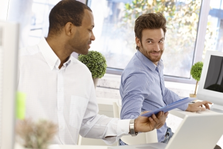 white color worker: Young male office workers sitting at desk, one passing folder to the other in bright office. Stock Photo