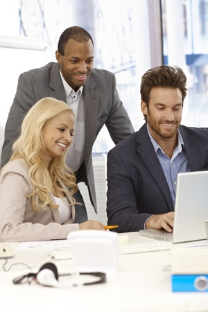 co work: Happy young businesspeople working together in bright office, using laptop computer, smiling. Stock Photo