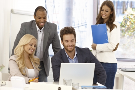 co workers: Happy team of young businesspeople working together, using laptop computer, smiling. Stock Photo