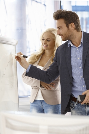 associates: Young businessman drawing diagram on whiteboard, female colleague watching.
