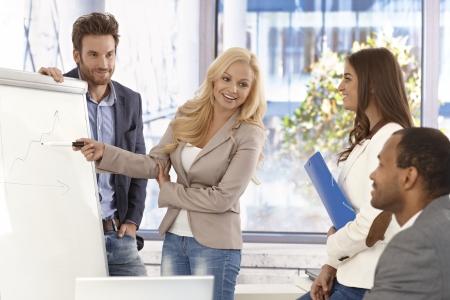 work together: Aantrekkelijke jonge zakenvrouw presenteren aan collega's op whiteboard, smiing. Stockfoto