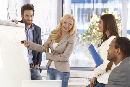 demonstrate: Attractive young businesswoman presenting to colleagues on whiteboard, smiing. Stock Photo