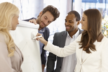 markerboard: Team of young businesspeople working together, using whiteboard, smiling happy.