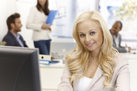 Portrait of happy young businesswoman sitting at desk, working with computer, smiling, looking at camera. Stock Photo - 17134056