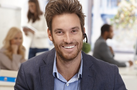 Closeup portrait of handsome male customer service representative smiling happy. photo