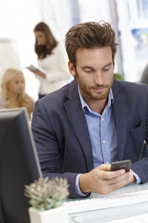 Young businessman sitting at desk in office, using mobilephone. Stock Photo - 17133925