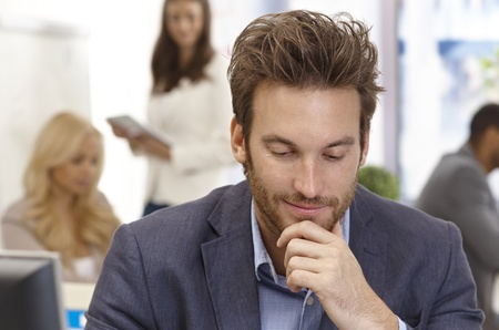 looking down: Young businessman thinking in office hand on chin, looking down.