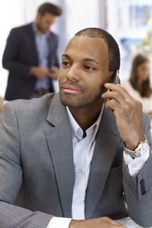 Portrait of handsome young black businessman talking on mobile phone, looking away. photo