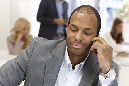 Closeup portrait of afro businessman talking on mobilephone in busy office. photo
