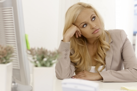 Beautiful blonde businesswoman sitting bored at desk, daydreaming. Stock Photo - 17134047