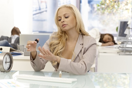 Pretty blonde woman sitting at desk in office, polishing nails, others sleeping at background. Stock Photo - 17133967