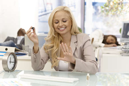 Happy blonde businesswoman sitting at desk in office looking satisfied her newly polished nails. Colleagues sleeping at background. Stock Photo - 17133957