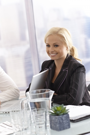 Portrait of attractive young businesswoman sitting by meeting table. Stock Photo - 17133958