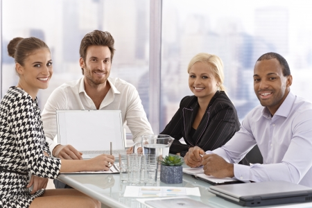 Happy young businesspeople sitting at meeting table, discussing business, smiling happy. photo