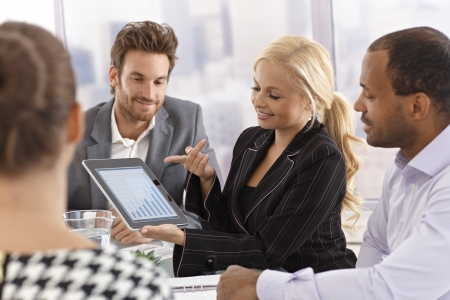 Young businesswoman using tablet to present business diagram at a meeting.